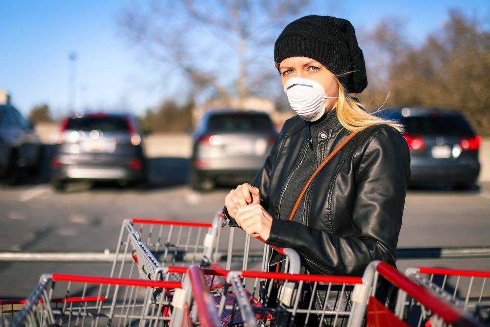 Una ragazza col carrello della spesa indossa la mascherina (foto di repertorio)