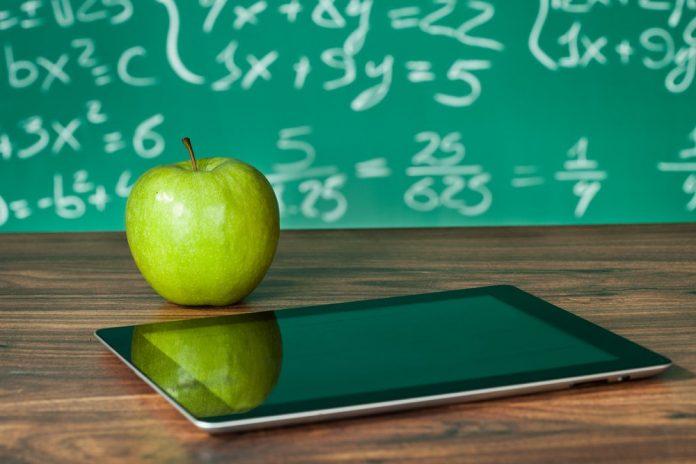 Una lavagna, un tablet e una mela (foto di repertorio)