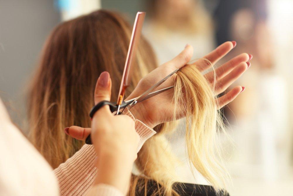 Una parrucchiera mentre taglia i capelli a una cliente (foto di repertorio)