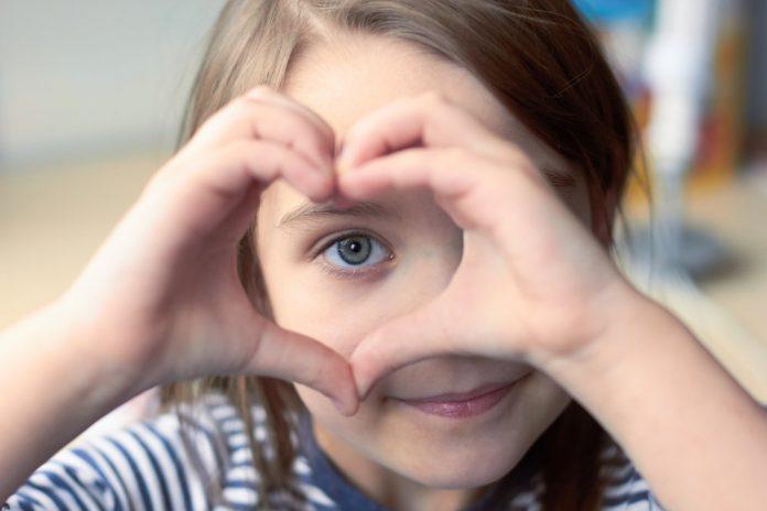 Una bambina crea un cuore con le mani attorno al suo occhio (foto di repertorio)