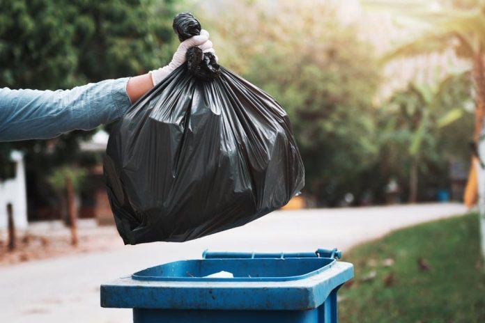 Un uomo getta i rifiuti nel bidone (foto di repertorio)