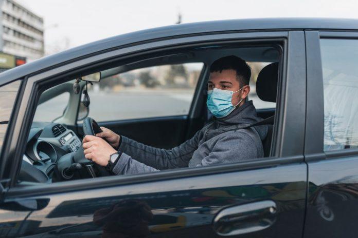 Uomo in macchina con la mascherina (foto di repertorio)