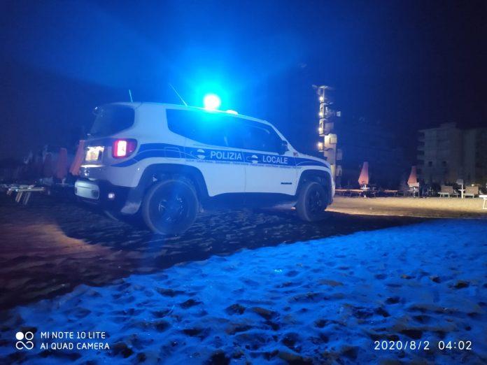 Polizia locale nella notte in spiaggia.