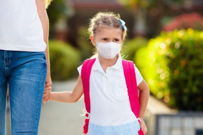 Bambina indossa la mascherina chirurgica prima di entrare a scuola (foto di repertorio)