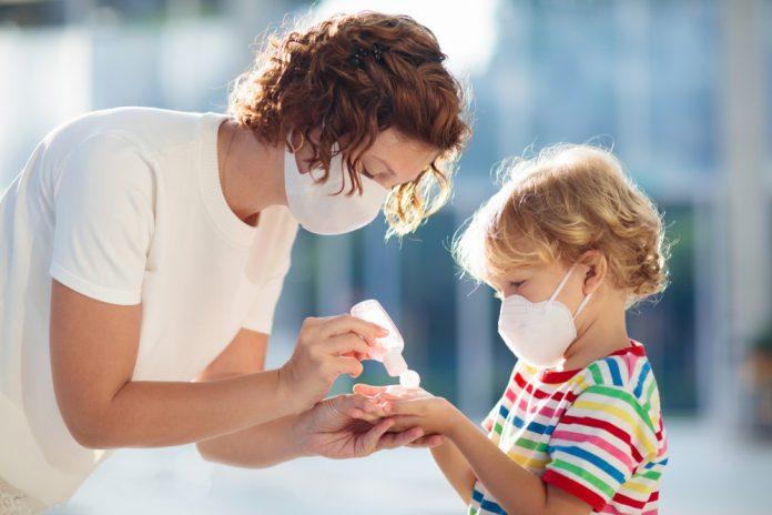 Mamma e figlio indossano le mascherine chirurgiche e usano il gel igienizzante per le mani (foto di repertorio)