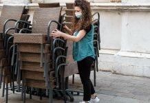 Una ragazza con la mascherina chirurgica impila le sedie di un locale (foto di repertorio Shutterstock.com)