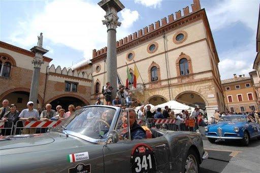 Giannantonio Mingozzi e Pietro Morini su Lancia Aurelia B24 in piazza a Ravenna.