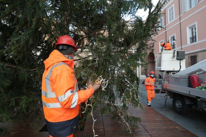 Operai mentre montano le luminarie sull'albero di Natale