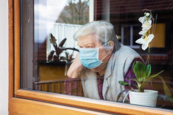 Un'anziana signora indossa la mascherina chirurgica e guarda fuori dalla finestra (foto di repertorio)