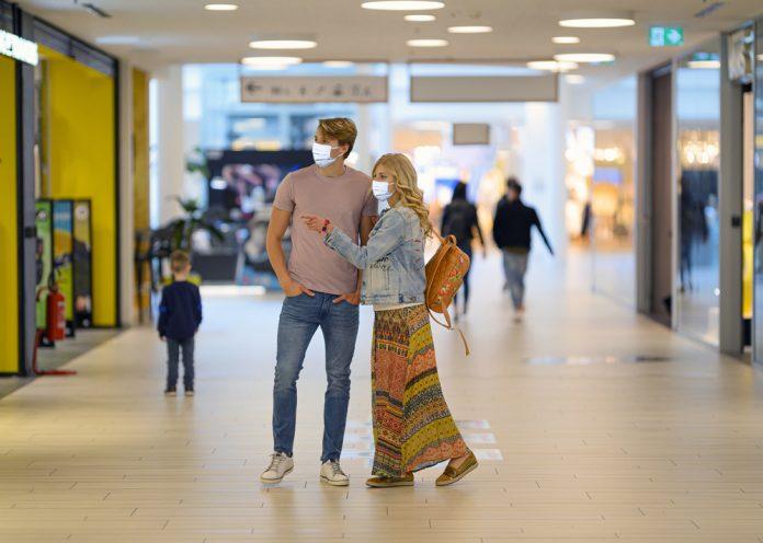 Una coppia al centro commerciale indossa le mascherine (foto di repertorio shutterstock)