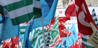 Bandiere dei Sindacati a una manifestazione (foto Giacomo M / Shutterstock.com)