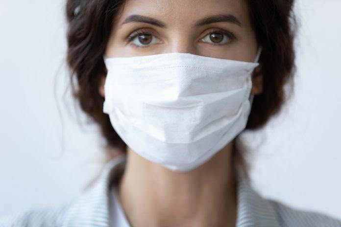 Una ragzza indossa la mascherina (foto di repertorio Shutterstock.com)