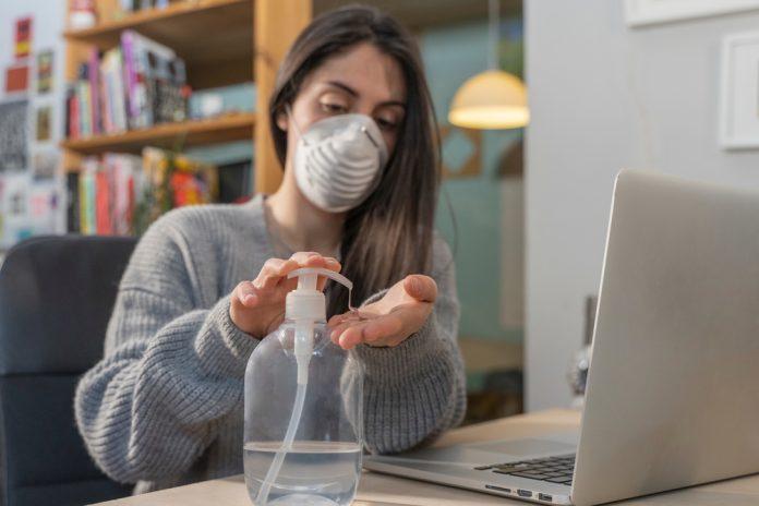 Una ragazza davanti al pc indossa la mascherina e si igienizza le mani (foto di repertorio Shutterstock.com)