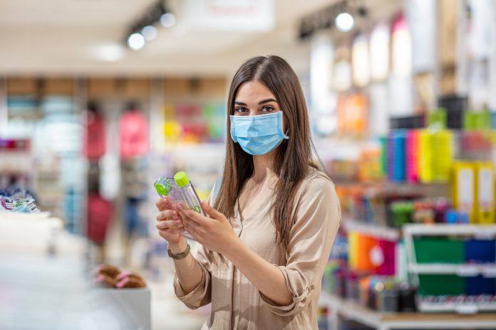 Una ragazza all'interno di un negozio indossa la mascherina (foto di repertorio Shutterstock.com)
