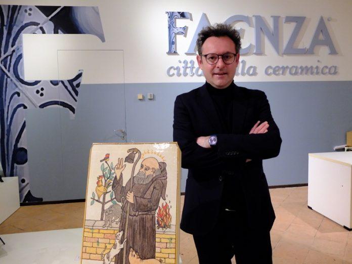 Massimo Isola con una ceramica dedicata al patrono dei ceramisti esposta nella vetrina della Pro Loco di Faenza