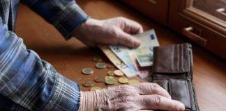 Un anziano estrae i soldi dal porafogli (foto di repertorio Shutterstock.com)