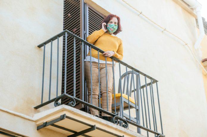 Una donna sul balcone parla al telefono mentre indossa la mascherina chirurgica (foto di repertorio Shutterstock.com)