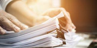 Un uomo sfoglia delle pile di fogli di carta (foto di repertorio Shutterstock.com)