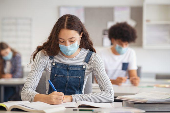 Una ragazza sul banco di scuole indossa la mascherina chirurgica