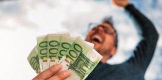 Un uomo esulta coi soldi in mano (foto di repertorio Shutterstock.com)